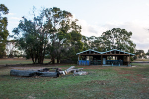 The camp kitchen blends well with the surrounding bush. The fire pit can be seen in the foreground.